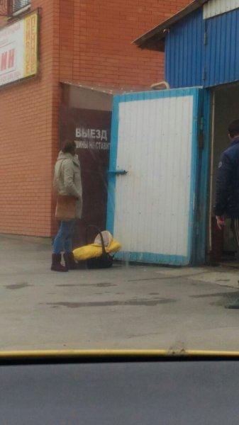 Уставшая горе-мамаша подперла люлькой с ребенком ворота автомойки